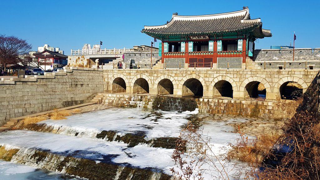 CompuertaHwahongmun(화홍문) de la Fortaleza Hwaseong en invierno con el río Suwoncheon congelado.