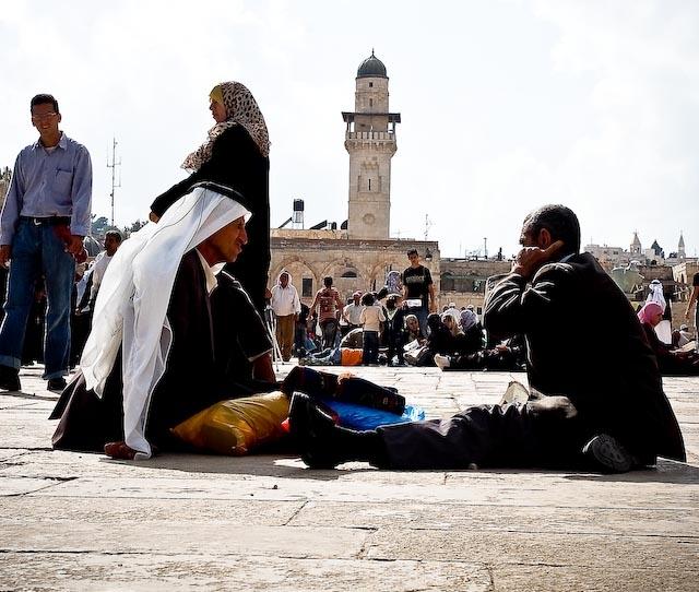 Ancianos sentados en el suelo en una plaza en Belén (Palestina), rodeados de familias, amigos y otros grupos de personas.