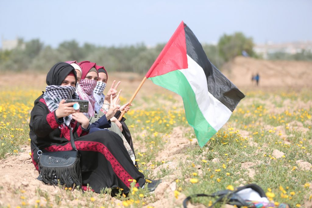Cuatro niñas en los campos de Palestina posan ante la cámara con su bandera palestina.